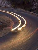 Un automobiliste conduit sur la route à la tombée de la nuit Photos stock