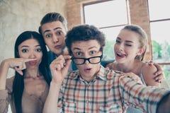 Un autoritratto di quattro genti felici allegre, havin dei tipi e delle ragazze fotografia stock libera da diritti