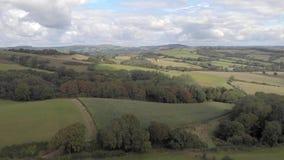 Un avant aérien révèle des images d'un paysage rural de collines ondulées de champs herbeux, de forêts et de champs de cultures s banque de vidéos