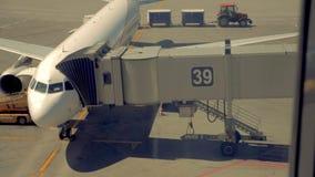 Un avión con un callejón especial está en una pista, preparándose para el vuelo 4K almacen de video