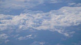 Un avión de pasajeros está volando en el cielo azul con las nubes metrajes