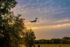 Un avión de pasajeros grande va en el aterrizaje en la puesta del sol tiroteo en el parque contra la perspectiva de árboles del o fotos de archivo libres de regalías