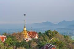 Un avión del microlight vuela por Wat Phrathat Doi Saket Imágenes de archivo libres de regalías