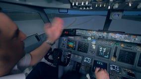 Un avión va en una pista, dos pilotos en una carlinga del simulador de vuelo almacen de metraje de vídeo
