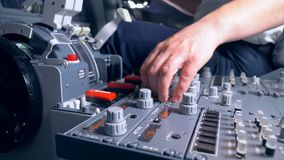 Un aviador está llevando a cabo su mano cerca de los botones de regla en un panel de la carlinga metrajes