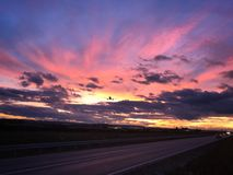 Un avion approche l'aéroport de Stuttgart pendant un coucher du soleil dramatique Photo stock