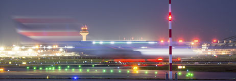 Un avion commençant la tache floue de vitesse à un aéroport la nuit Images stock