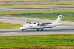 Un avion de passagers de turbopropulseur débarque sur la piste à l'aéroport, l'inverse Photo libre de droits