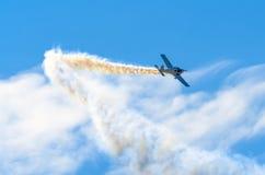 Un avion de turbopropulseur avec une trace de fumée dans un ciel ensoleillé de nuage Photo stock