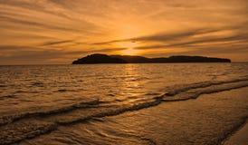 Un avion directement dans le coucher de soleil de la mer photos stock