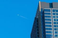 Un avion passe haut au-dessus d'un gratte-ciel grand de New York City avec une façade en verre et concrète image libre de droits