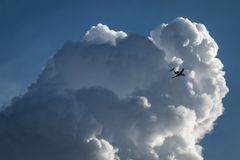 Un avion vole à côté d'un grand cumulus avant le débarquement à un aéroport photographie stock libre de droits