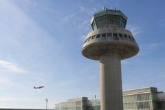 Un avion vole à côté de tour de contrôle à l'aéroport de Barcelone, PS Photo libre de droits