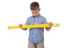 Un ayudante pensativo lindo del constructor en una camisa a cuadros azul sostiene una regla amarilla grande de la construcción Fotos de archivo libres de regalías