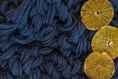 Un azul hizo punto el fondo combinado en un estilo acogedor con las rebanadas de naranja secada Endecha plana imagen de archivo libre de regalías