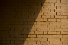 Un bâti d'ombre de midi sur un mur de briques brun Photographie stock