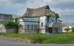 Un bâtiment colonial abandonné de style de gouvernement avec l'élevage d'herbe de mauvaise herbe Image stock