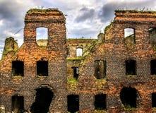 Un bâtiment déchiré par la guerre de brique rouge, fenêtres cassées, ciel sombre Le concept des conséquences de la guerre et de l Images libres de droits