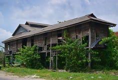 Un bâtiment en bois privé abandonné de style traditionnel avec l'herbe de mauvaise herbe s'élevant en Asie du Sud-Est Photographie stock libre de droits