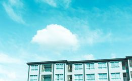 Un bâtiment sous les nuages pelucheux blancs et le ciel en pastel bleu dans un jour ensoleillé image libre de droits
