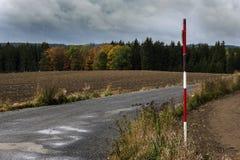 Un bâton rouge et blanc se tenant près du chemin entre les champs Photographie stock libre de droits