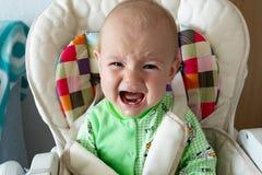 Un bébé an était bouleversé et pleurer Petit garçon dans un costume vert clair avec des moutons photo libre de droits