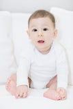 Un bébé adorable et heureux regardant l'appareil-photo sur les oreillers blancs Image libre de droits
