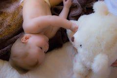 Un bébé curieux avec un ours blanc de jouet Photos libres de droits