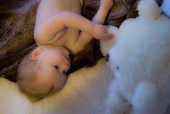 Un bébé curieux avec un ours blanc de jouet Image libre de droits