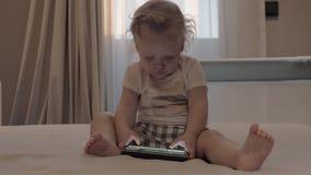 Un bébé dans des shorts à carreaux se reposant sur un lit avec un comprimé devant elle clips vidéos