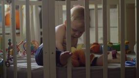 Un bébé dans le pantalon bleu jouant avec un jouet dans une huche banque de vidéos
