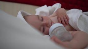 Un bébé de sommeil avec la bouteille se trouve sur le lit avec la literie blanche, mouvement lent banque de vidéos