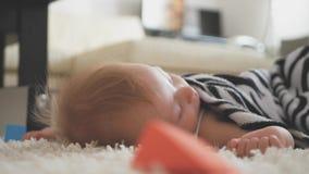 Un bébé doux dormant dans le plancher à la maison banque de vidéos