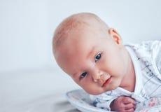 Un bébé drôle avec de beaux yeux se trouve sur son estomac et sourit images stock