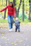 Un bébé garçon an en parc d'automne apprenant à marcher avec sa mère Images libres de droits