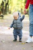 Un bébé garçon an en parc d'automne apprenant à marcher avec sa mère Photo libre de droits