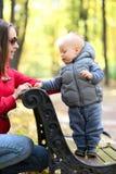 Un bébé garçon an en parc d'automne avec sa mère Images libres de droits