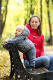 Un bébé garçon an en parc d'automne avec sa mère Image stock