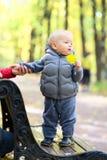 Un bébé garçon an en parc d'automne avec sa mère Images stock