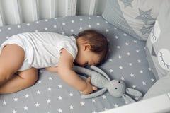Un bébé garçon an se situant dans un lit rond Images stock