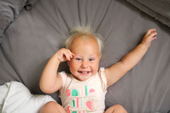 Un bébé an heureux s'étendant dans le lit Photographie stock libre de droits