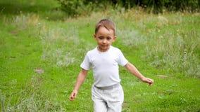Un bébé mignon court sur l'herbe verte dans le mouvement lent banque de vidéos