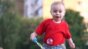 Un bébé mignon dans des shorts de denim fonctionnant derrière des bulles de savon dans le mouvement lent dehors banque de vidéos