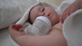 Un bébé mignon de sommeil avec la bouteille vide se trouve sur le lit avec la literie blanche banque de vidéos