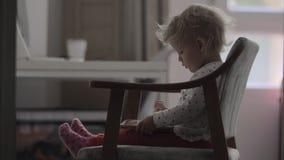 Un bébé s'asseyant dans une chaise avec un comprimé sur ses recouvrements clips vidéos