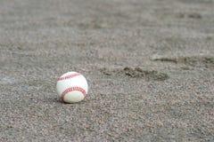 Un béisbol en el área de la pista de aterrizaje del campo de deporte foto de archivo