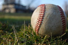 Un béisbol gastado en la hierba Fotos de archivo libres de regalías