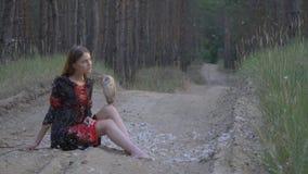 Un búho marrón claro se sienta en la rodilla de una muchacha en un vestido mientras que las plumas caen del cielo, tiroteo de la  metrajes