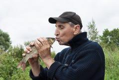 Un bacio fortunato del pescatore un cavedano Fotografia Stock