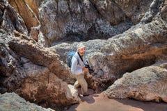 Un backpacker sonriente va abajo de la trayectoria entre las rocas, con la cámara Foto de archivo
